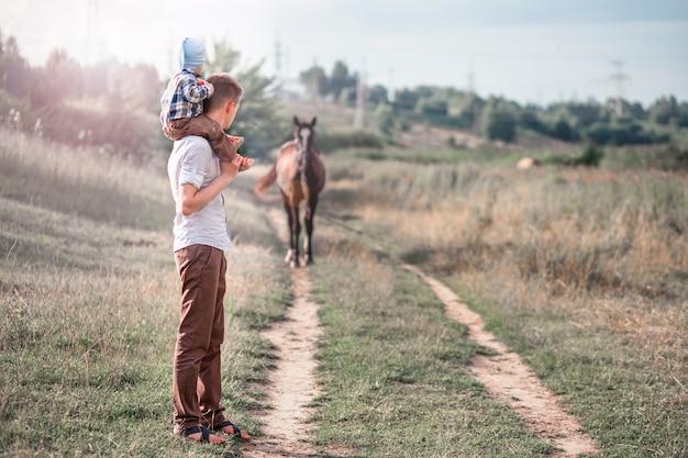 Petit fils et son père regardant le cheval Photo Premium