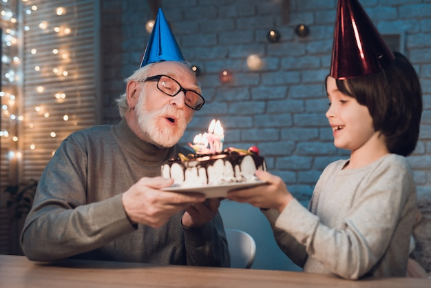 Petit-fils Soufflant Des Bougies Sur Le Gâteau D'anniversaire Photo Premium