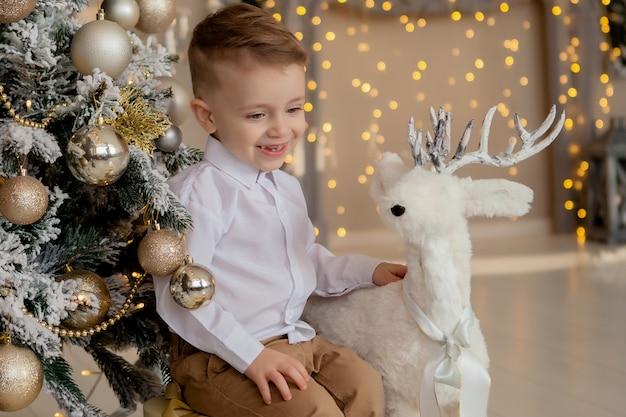 Petit garçon de 2 ans étreint une décoration élégante en bois de cerf de noël près de la branche dépolie, suspendu à un arbre de noël, belle alternative au décor traditionnel version du nouvel an scandinave Photo Premium