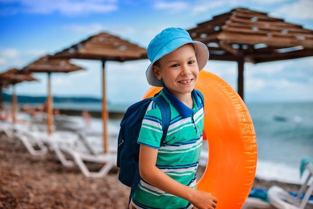 Petit garçon de 6 ans portant un chapeau gonflable avec un cercle orange Photo Premium