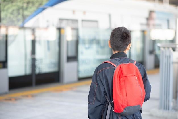 Petit Garçon, Acheter Un Billet électrique Et Marcher Dans La Gare Du Ciel Public En Famille Photo Premium