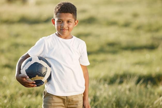 Petit Garçon Africain. Enfant Dans Un Parc D'été. Enfant Avec Ballon De Socer. Photo gratuit