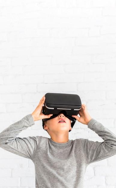 Petit garçon à l'aide de lunettes de réalité virtuelle Photo gratuit