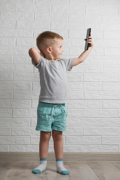 Petit Garçon à L'aide D'une Maquette De Téléphone Photo gratuit