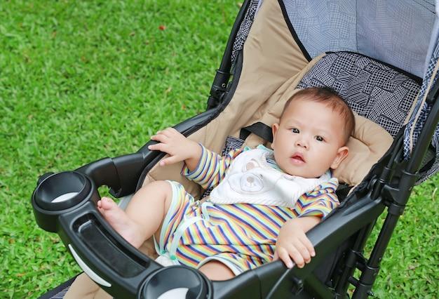 Petit garçon asiatique assis dans la poussette du jardin vert. Photo Premium