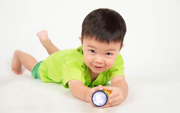 Un petit garçon asiatique jouant des blocs de bois portent un ingénieur de casque Photo Premium