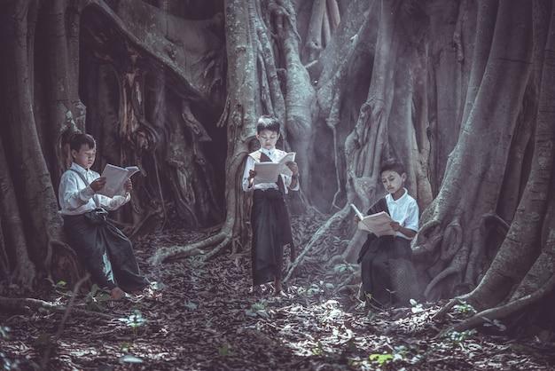 Petit garçon asiatique lisant un livre sous un grand arbre dans les zones rurales Photo Premium