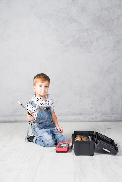 Petit garçon assis avec une clé Photo gratuit