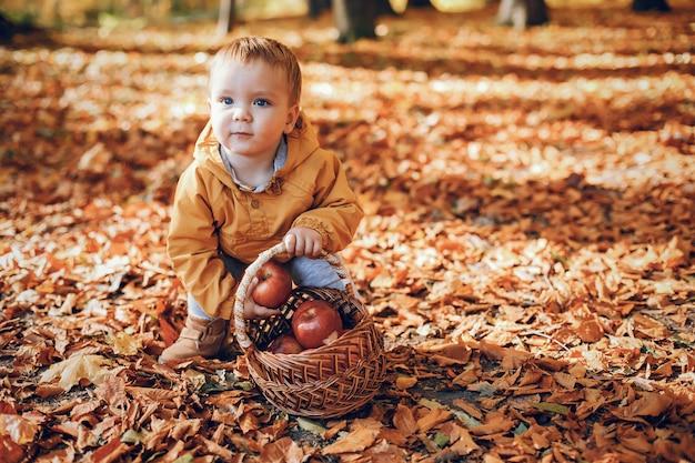 Petit garçon assis dans un parc en automne Photo gratuit