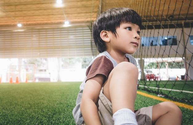 Petit garçon assis dans le terrain de sport de football Photo Premium