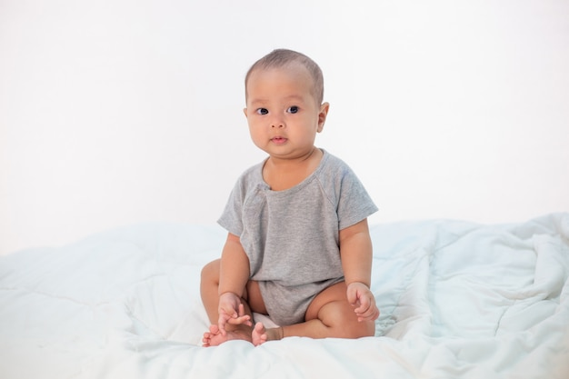 Le petit garçon assis sur le lit Photo gratuit