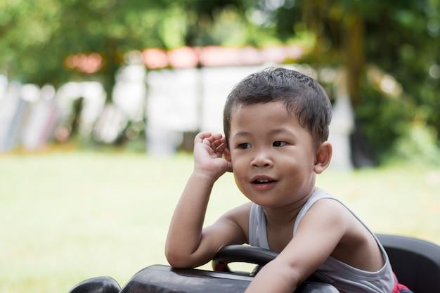 Petit garçon au volant d'une voiture rouge avec le volant. Photo Premium