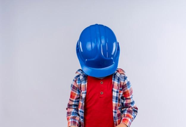 Un Petit Garçon Aux Cheveux Blonds Portant Une Chemise à Carreaux Fermant Son Visage Avec Un Casque Bleu Sur Un Mur Blanc Photo gratuit