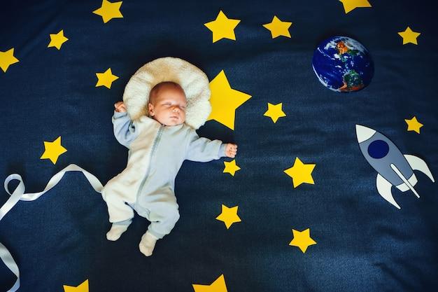 Petit garçon bébé dort dans un costume de l'astronaute du ciel étoilé Photo Premium