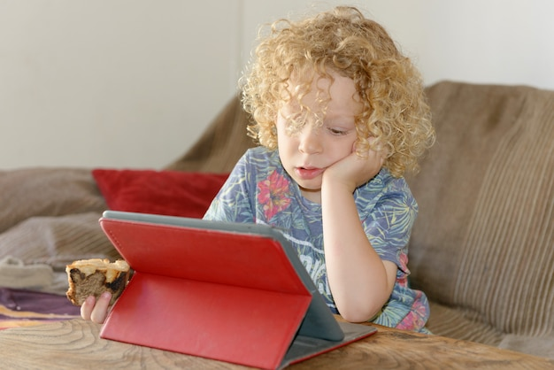 Petit garçon blond à l'aide d'une tablette Photo Premium