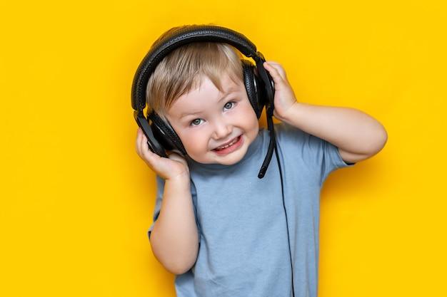 Petit garçon blond caucasien mignon dans les écouteurs sur jaune Photo Premium