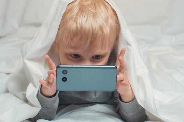 Petit garçon blond enfouit son nez dans son smartphone. allongé dans son lit et caché sous les couvertures. gadget loisirs Photo Premium