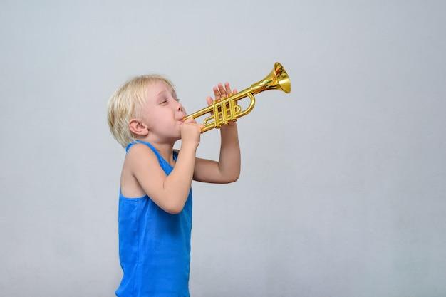 Petit garçon blond mignon jouant de la trompette Photo Premium