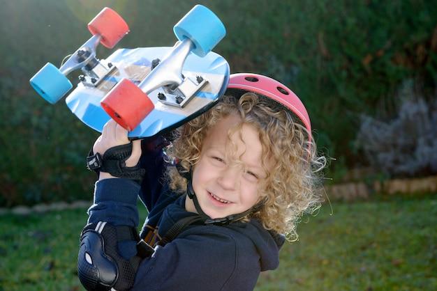 Petit garçon blond avec skateboard Photo Premium