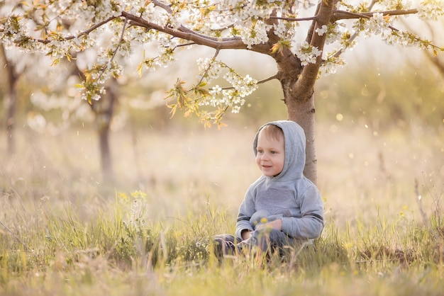 Petit Garçon Blond En Sweat-shirt Gris Avec Une Capuche Sur La Tête Se Trouve Dans L'herbe Verte Sous L'arbre En Fleurs Photo Premium