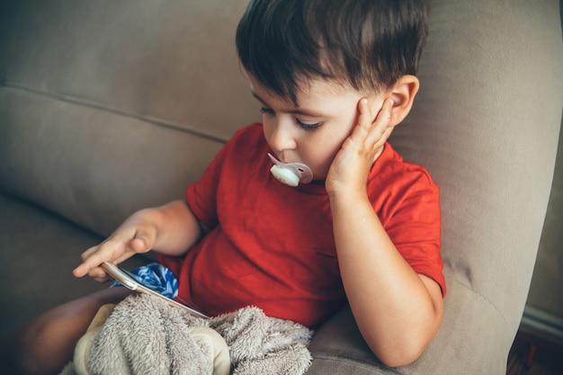 Petit Garçon Caucasien Assis Sur Le Lit Et Regardant L'écran Du Téléphone Tout En Tenant Une Mangeoire Dans La Bouche Photo Premium