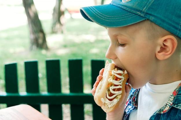 Petit garçon caucasien manger hamburger Photo Premium