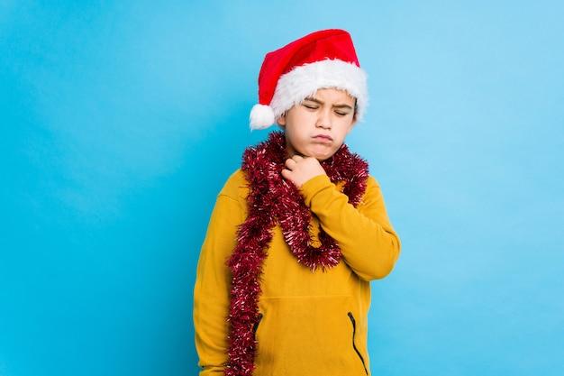 Petit garçon célébrant le jour de noël portant un bonnet de noel isolé souffre de douleurs à la gorge dues à un virus ou à une infection. Photo Premium