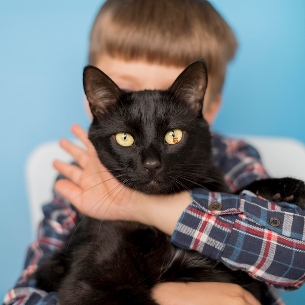 Petit Garçon Avec Chat Noir Photo gratuit