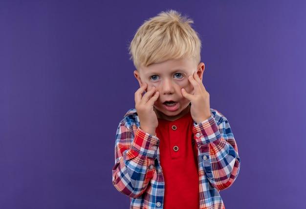Un Petit Garçon Choqué Aux Cheveux Blonds Portant Une Chemise à Carreaux Tenant La Main Sur Son Visage Sur Un Mur Violet Photo gratuit