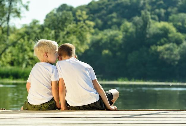 Petit garçon chuchote à l'autre oreille, assis sur la rive de la rivière. Photo Premium