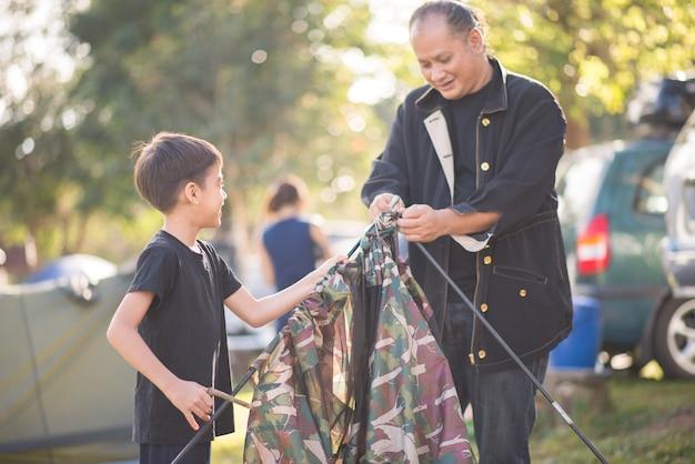 Petit garçon construit une tente pour le camping avec l'heure d'été des vacances en famille Photo Premium