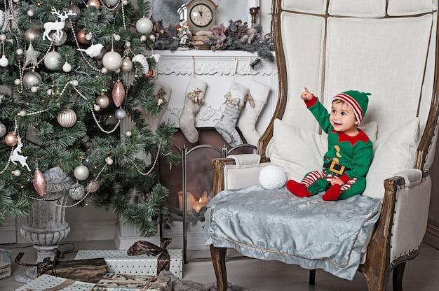 Petit garçon en costume elfe assis sur la chaise à l'intérieur de la maison au coin du feu et attendant le père noël Photo Premium
