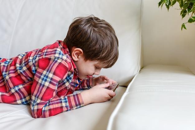 Petit garçon couché sur le lit jouer un téléphone intelligent Photo Premium