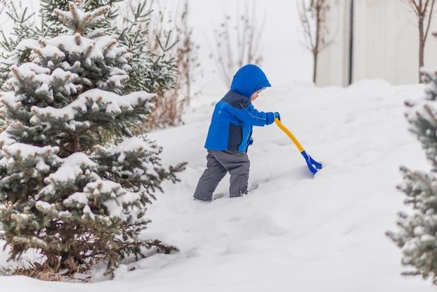 Un petit garçon creuse la neige avec une pelle en hiver. Photo Premium
