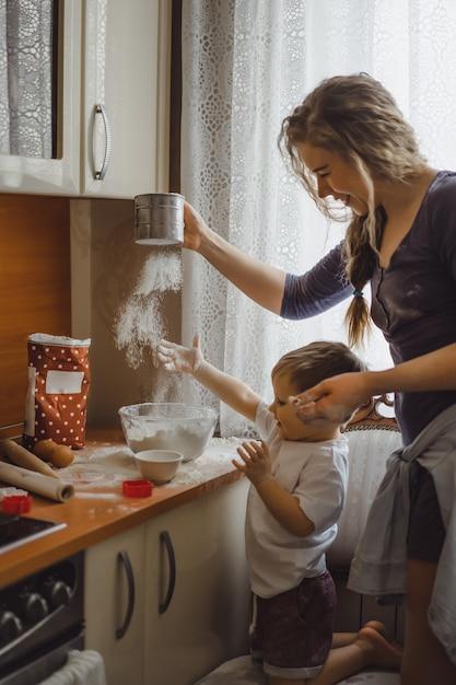 Petit garçon dans la cuisine aide maman à cuisiner. l'enfant est impliqué dans la cuisine. Photo gratuit