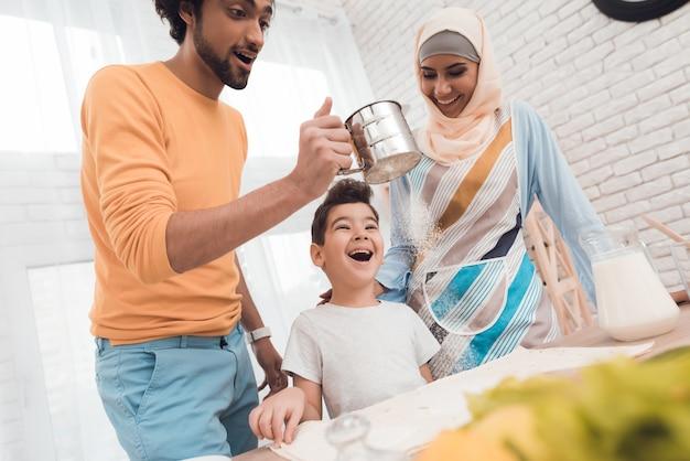 Un petit garçon dans la cuisine avec sa famille. Photo Premium