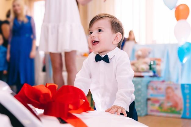 Petit Garçon, Dans, élégant, Vêtements, Sourire, Et, Debout, Près, Les, Voiture Photo Premium
