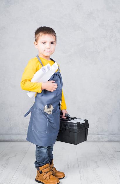 Petit garçon debout avec une boîte à outils et des rouleaux de papier Photo gratuit