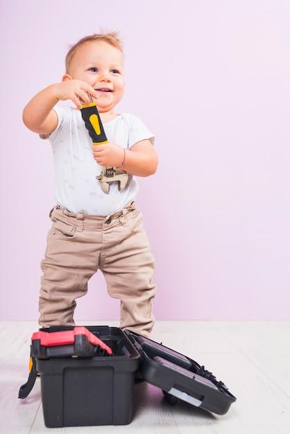 Petit garçon debout avec une clé Photo gratuit