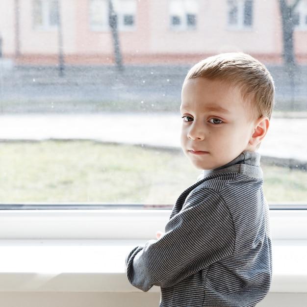 Petit garçon debout près de la fenêtre Photo Premium