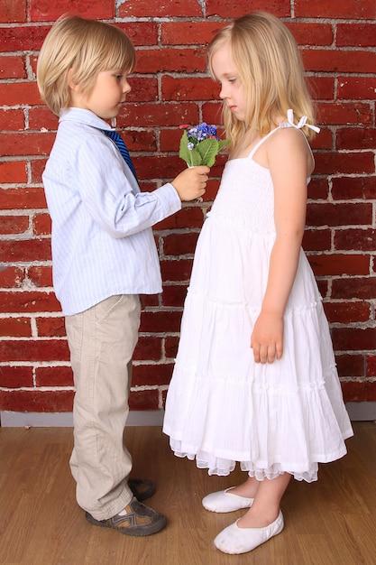 Petit Garçon Donne à Une Fille Un Beau Bouquet De Fleurs. Photo Premium