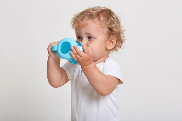 Petit Garçon Avec De L'eau Potable Tasse Bébé En Plastique Bleu, Enfant Assoiffé En T-shirt Posant Isolé Sur Espace Blanc Photo Premium