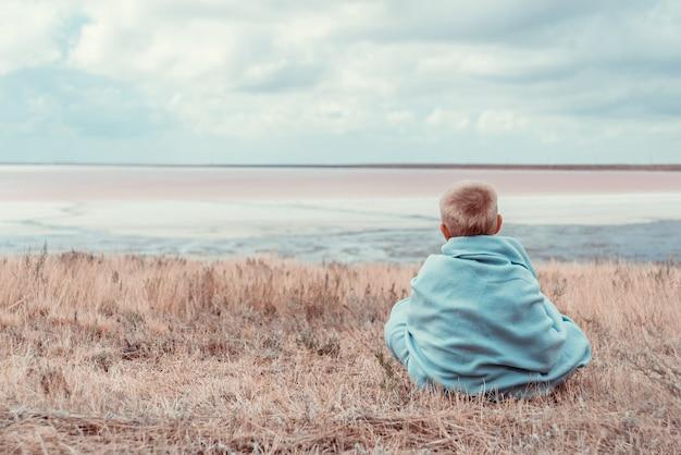 Petit garçon est assis près de la mer dans une couverture chaude Photo Premium