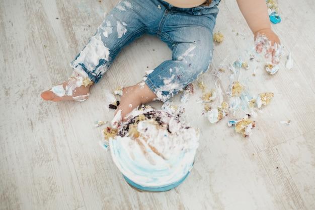 Le petit garçon est tout pris avec un gâteau Photo gratuit