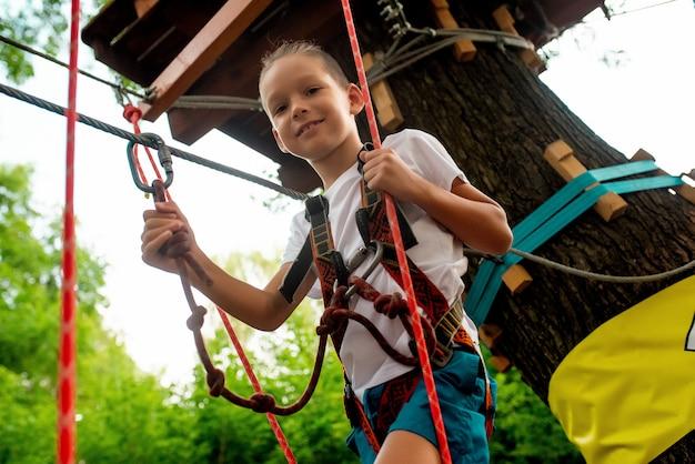 Petit garçon exécute un parcours du combattant dans un parc de corde Photo Premium