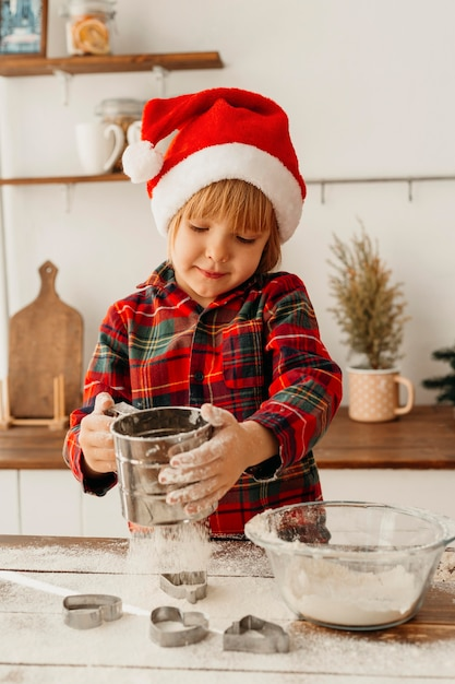 Petit Garçon Faisant Un Biscuit De Noël Photo gratuit