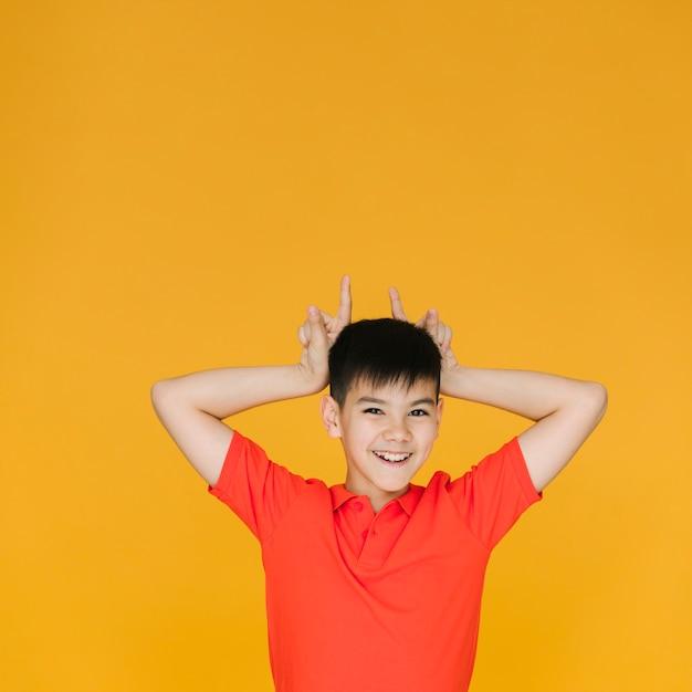 Petit garçon faisant des cornes avec ses doigts Photo gratuit