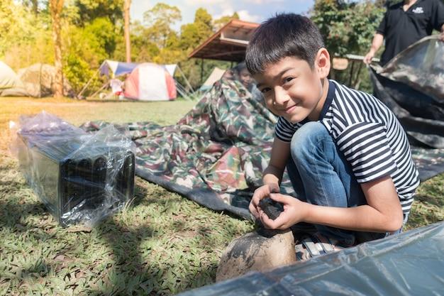 Petit garçon faisant une tente de camp activité d'été en plein air avec la famille Photo Premium