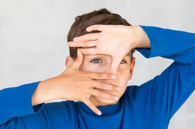 Petit garçon fait un cadre avec ses doigts Photo gratuit