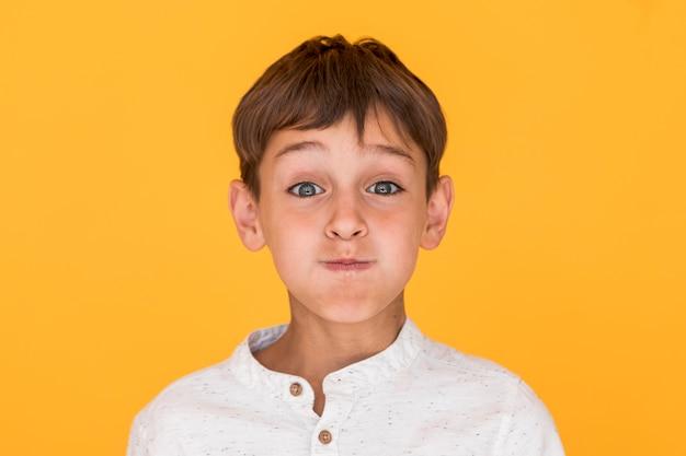 Petit garçon fait une grimace Photo gratuit